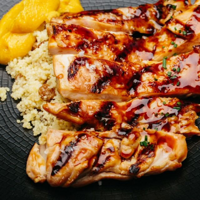 Sliced, teriyaki-glazed chicken leg with cous-cous